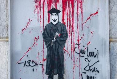 A student in graduation clothes. The writing says humanity is better than war. Photo.