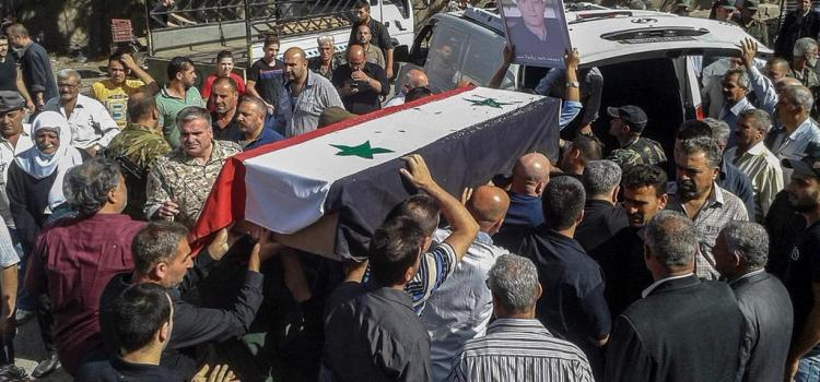 Syrian mourners carry coffins of victims of an ISIS attack on Sweida, 26 July 2018. SANA